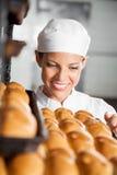 Baker Looking At Fresh Broden in Bakkerij royalty-vrije stock afbeeldingen