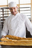 Baker looking at freshly baked baguettes Royalty Free Stock Images