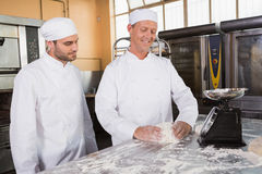 Baker looking his colleague kneading dough Stock Photo
