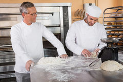 Baker looking his colleague kneading dough Stock Image