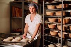 Baker maakt handinsnijdingen op het deeg voor het brood De Vervaardiging van Brood bakkerij royalty-vrije stock foto