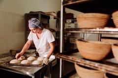 Baker maakt handinsnijdingen op het deeg voor het brood De Vervaardiging van Brood bakkerij royalty-vrije stock afbeeldingen