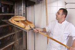 Baker makes the bread. Baker keeps the bread fresh from the oven Stock Images