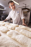 Baker makes the bread. Kneaded in the oven Royalty Free Stock Photography