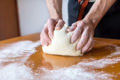 Baker makes bread on the table Royalty Free Stock Photography