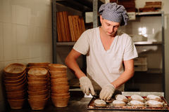 A Baker makes manual incisions on the dough for the bread. The Manufacture Of Bread.Bakery Stock Photos
