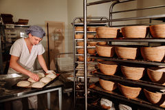 A Baker makes manual incisions on the dough for the bread. The Manufacture Of Bread.Bakery Royalty Free Stock Photos