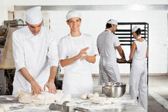 Baker Making Dough Balls By Male Colleague In Bakery. Portrait of female baker making dough balls by male colleague in bakery Stock Images