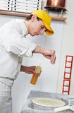 Baker making dough for Pizza. One chef baker in white uniform making bakery dough for pizza at kitchen royalty free stock photography