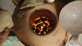 Baker making turkish pita bread in tandoor, clay oven. Baking process. Baker making turkish pita bread in tandoor, clay oven. Baking process stock video footage