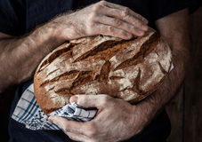 Baker man holding rustic loaf of bread in hands Stock Photo