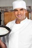 Baker masculin sûr Holding Dough Tray At Bakery Photos libres de droits
