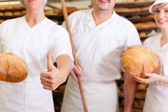 Baker met zijn team in bakkerij Royalty-vrije Stock Foto's
