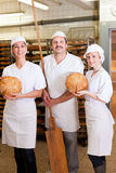 Baker met zijn team in bakkerij Stock Foto