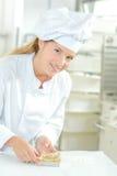 Baker mettant des contacts de finale au dessert image libre de droits