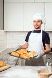 Baker montrant le croissant Photo stock