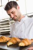 Baker montrant le plateau du croissant frais Photos stock