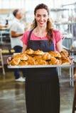Baker montrant le plateau du croissant frais Photo libre de droits