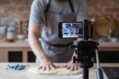 Baker online training class man shoot video phone. Baker online courses. food preparing and culinary training class concept. smiling bearded chef kneading dough royalty free stock photos