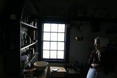 The Baker. Pioneer baker preparing flour in antique kitchen at Kings Landing historic site in New Brunswick Stock Photo