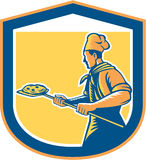 Baker Pizza Maker Holding Peel Pizza Shield. Illustration of a baker pizza maker holding a peel with pizza pie viewed from side set inside shield crest done in Royalty Free Stock Photo