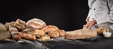 Baker placing an empty wooden paddle on a table. Ready fore placing dough for baking with a display of speciality bread alongside stock photography