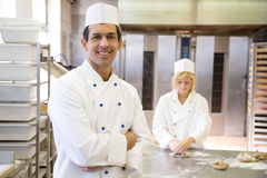 Baker posing in bakery or bakehouse. Another baker is working in the background Royalty Free Stock Images