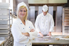 Baker posing in bakery or bakehouse. Another baker is working in the background Royalty Free Stock Photography