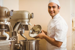 Baker pouring flour into large mixer Stock Images