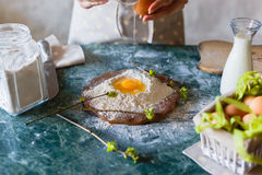 The baker pours the raw egg into the funnel in the flour on the table Royalty Free Stock Images