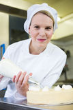 Baker prepares cake in bakehouse with whipped cream. Female baker or confectioner prepares cake with whipped cream Stock Photos