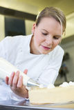 Baker prepares cake in bakehouse with whipped cream. Female baker or confectioner prepares cake with whipped cream Stock Images