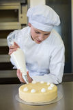 Baker prepares cake in bakehouse with whipped cream. Female baker or confectioner prepares cake with whipped cream Stock Photography