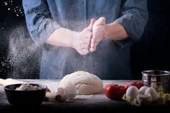 Baker prepares the dough on table Stock Image