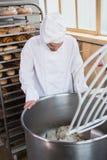 Baker preparing dough in industrial mixer Stock Photo