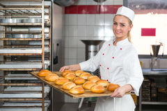 Baker presenting tray with pastry or dough at bakery Stock Photos
