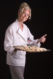 Baker Proud with Batch. Passive posed attractive female Pastry Chef gives thumbs up as holding hot tray of freshly baked cookies Stock Images