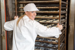 Baker pushing rack full of bread into the oven Stock Photo