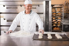 Baker putting dough on baking tray. In the kitchen of the bakery stock images