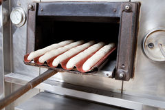 Baker putting dough into the oven Stock Images