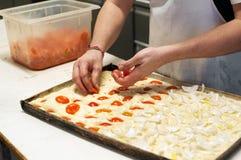 Baker putting ingredients on focaccia Royalty Free Stock Photos