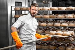 Baker putting with shovel bread loafs at the manufacturing royalty free stock photo