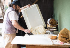 Baker razdelyvet dough for baking bread Royalty Free Stock Photos