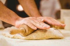 Baker rolling dough at a counter Royalty Free Stock Photos