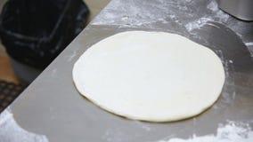 Baker rolt skillfully pizzadeeg stock footage