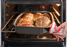Baker's hand with bread in oven Royalty Free Stock Photos