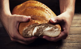 Baker's hands with a bread Royalty Free Stock Photography