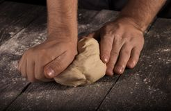 Baker`s hands kneaded ball of dough on table royalty free stock images