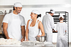 Baker's Looking At Each Other While Working In Bakery Stock Image