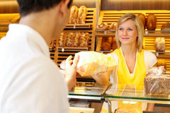 Baker's shop shopkeeper gives bread to customer Stock Photo